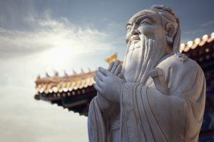Close-up of stone statue of Confucius, pagoda roof in the background